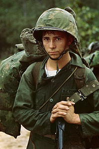 man wearing military helmet and uniform while carrying bag