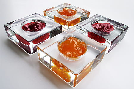 four square clear glass containers filled with substances