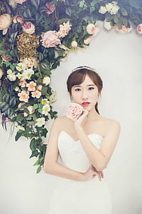 woman wearing white sweetheart neckline dress holding pink rose
