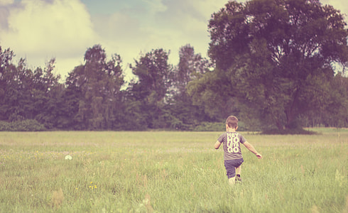boy running on grass field near trees