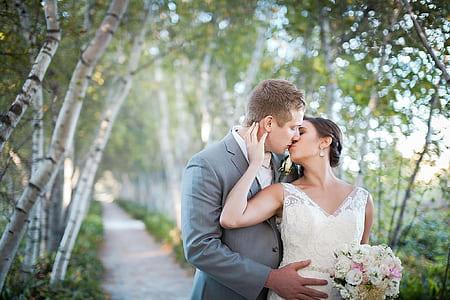 man kissing woman wearing white wedding dress