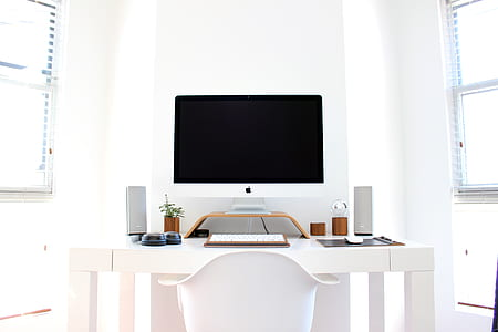 silver iMac beside Apple Keyboard on white wooden table