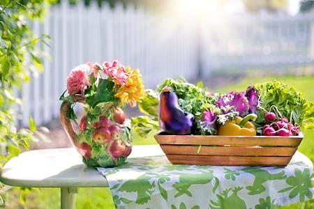 petaled on vase beside vegetables on the basket