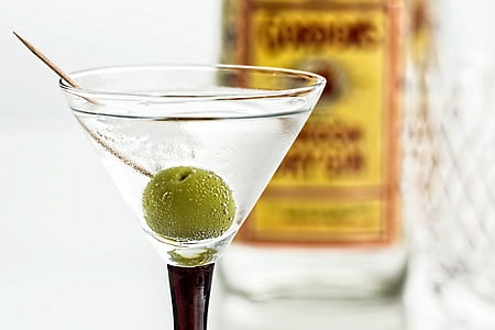 close-up photo of cocktail glass with white wine and green cherry top