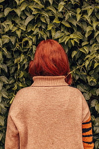 woman with red hair in gray, orange, and black sweater facing on green plant