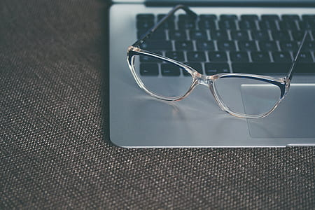 clear framed eyeglasses on silver MacBook