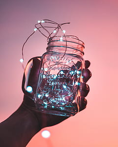 person holding clear glass mason jar with string light
