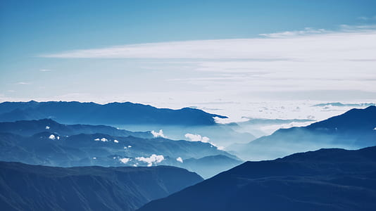 aerial photo of mountains under white clouds and blue sky