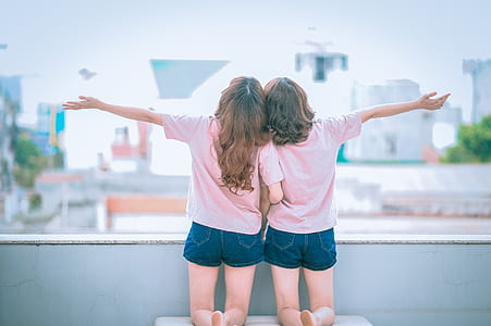 two girl wearing pink top kneeling on white chair