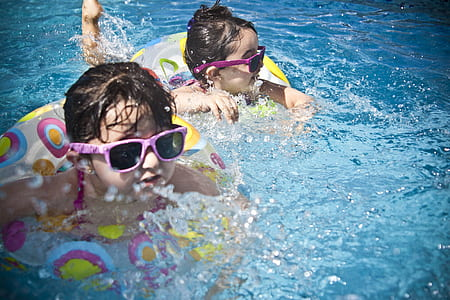 two boy and girl with pink sunglasses swimming