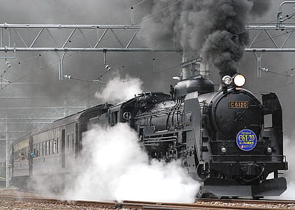 grayscale photograph of train with heavy smoke