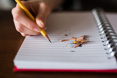 person writing in ruled paper