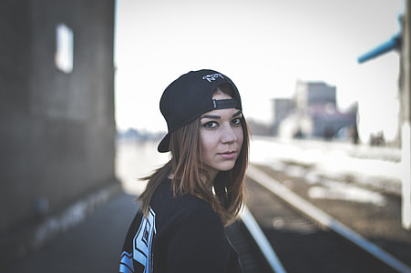 shallow focus photography of woman in black shirt wearing black cap