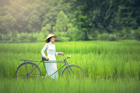 woman wearing brown hat while holding bike