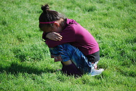 girl wearing maroon long-sleeved top and blue jeans sitting on green grasses during daytime