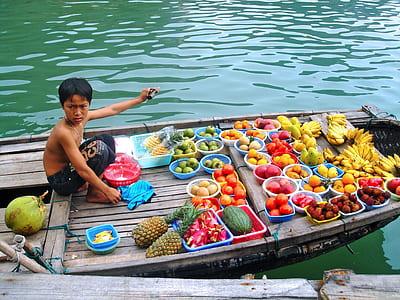 boy wearing black pants near fruits