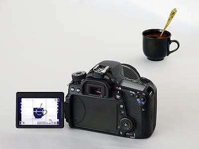 black DSLR camera capturing black ceramic mug with gold-colored spoon