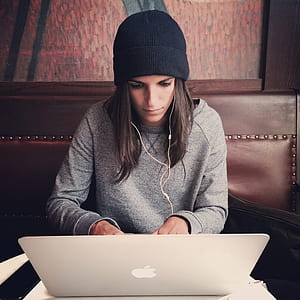 woman wearing black knit cap leaning MacBook