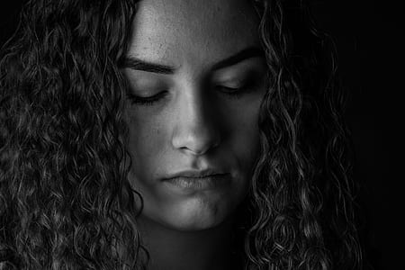 woman in curly hair closing her eyes