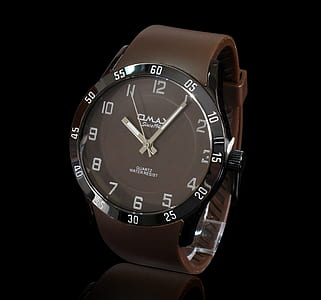 photo of round black analog watch with brown leather strap