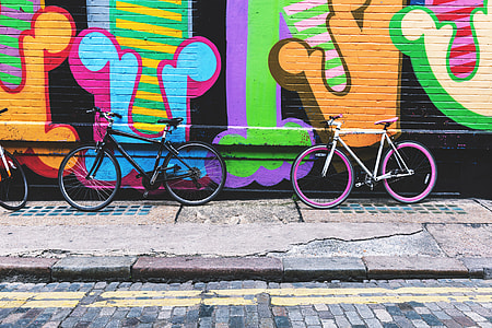 Bicycles stand against a street-art covered wall in the city