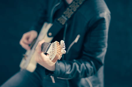 man playing guitar wearing black leather jacket