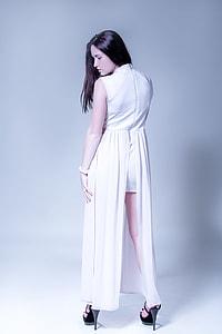 women wearing white sleeveless dress standing against white wall