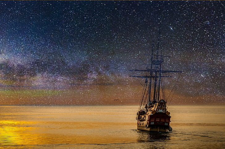 painting of ship with stars on night sky