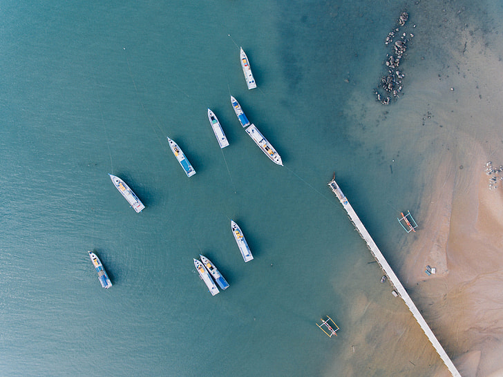 aerial photography of 10 yacht sailing on green ocean near seashore