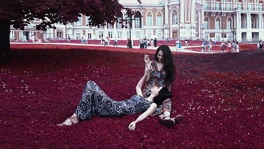 two women on red grass field