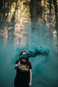 woman wearing black crew-neck with green smoke