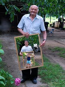 photo of man holding photo of man wearing white shirt holding photo frame