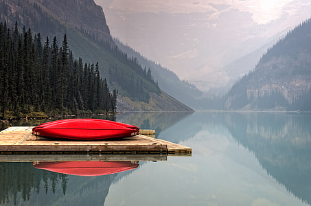 red canoe on brown wooden dock during daytime
