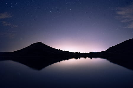 silhouette photo of mountain reflecting body of water