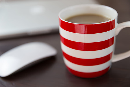 Coffee, computer and mouse on office desk