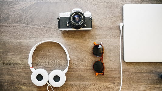 fly lay photography of headphones, MILC, laptop, and wayfarer sunglasses