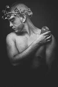 greyscale photo of topless man wearing leaf headdress while holding apple