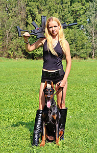 woman in black tank top and shorts holding rifle and black and tan Doberman pinscher at daytime