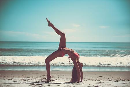 photo of woman bend on sand near beach
