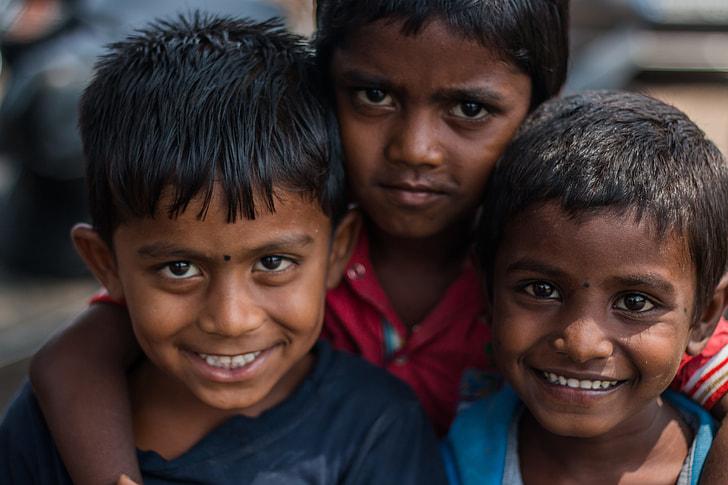 selective focus photography of three boys