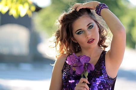 woman wearing purple tank top doing post holding flower