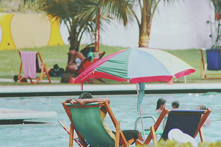 Person Lying on Bench Near Swimming Pool