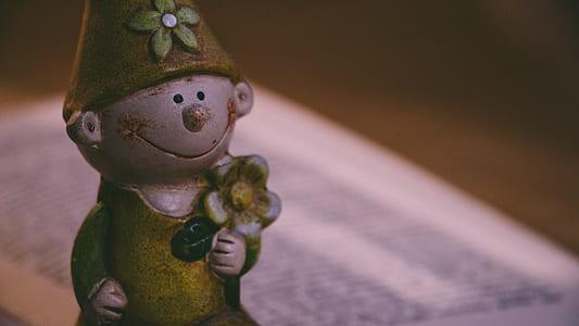 Closeup Photo of Boy Holding Flower Figurine