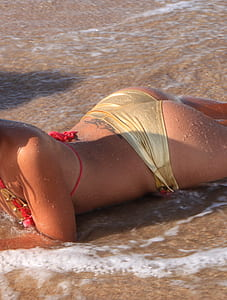 woman in yellow-and-red 2-piece bikini on beach during daytime