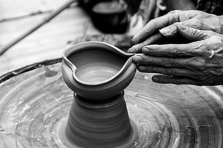 person's hand molding clay vase