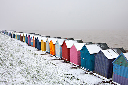 Winter-time snow covered scene of some beach huts on the Kent Coast in England