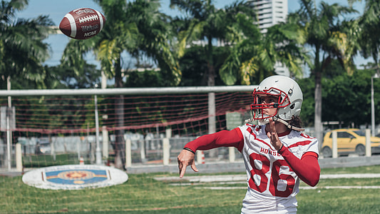 man wearing red and white 86 football jersey throwing football