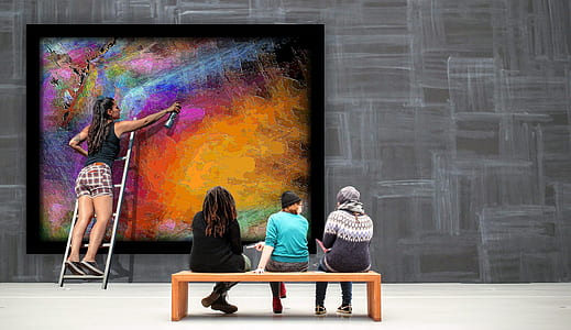 three people sitting near woman painting wall