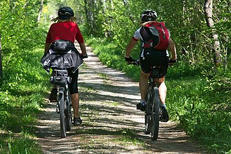 two person wearing red shirt biking during daytime