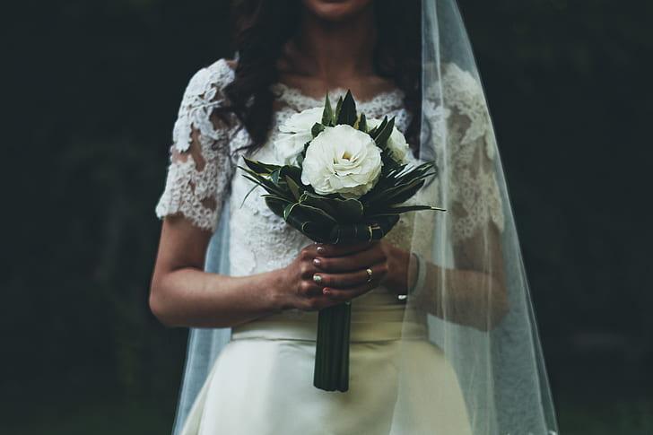 woman wearing wedding dress holding white flower bouquet